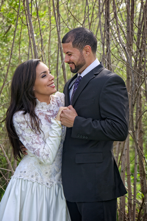 Still in wedding dress and suit, a young Hispanic couple hold hands and look affectionately into each others eyes in a romantic setting of tall branches and twigs   Zdjęcie Seryjne