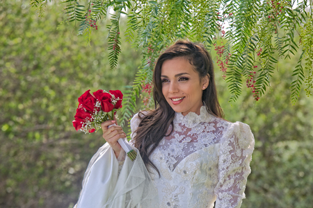 A gorgeous young Hispanic bride in a flowery wedding dress holds a rose bouquet and is framed with drooping leaves from a tree   Zdjęcie Seryjne