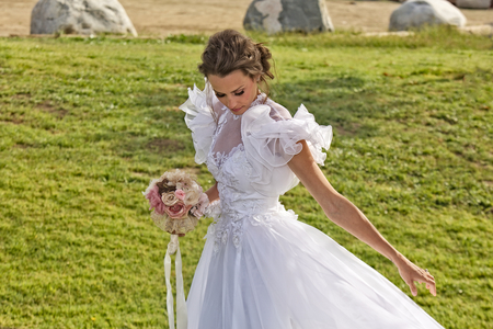 A young glamorous bride in a white dress with puffy sleeves stands in the meadow of a park looks down Zdjęcie Seryjne