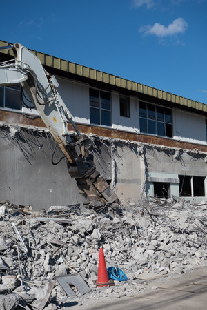 Building Being Demolished by an Excavator (Vertical)