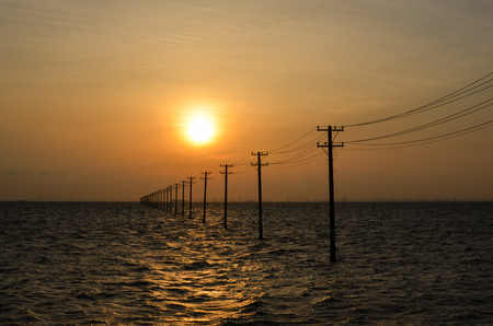 Sunset Over Utility Poles in a Sea
