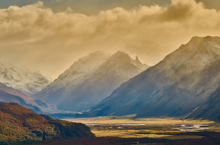 A view of the mountains and the valley, which illuminates the autumn sun making its way through the clouds. Argentine Patagonia in Autumn