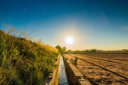 View of agricultural fields and buildings near Valencia before sunset. Spain Stock Photo