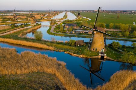 Aerial view of windmills in the Kinderdijk area during sunset. Spring in Holland. Фото со стока