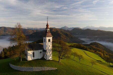 Luftaufnahme der Hügel, des bunten Waldes im Nebel und der Kirche von Sv Tomaz. Sonnenaufgang in Slowenien im Herbst