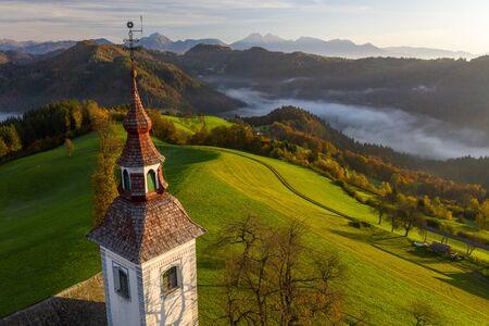 Luftaufnahme der Hügel, des bunten Waldes im Nebel und der Kirche von Sv Tomaz. Sonnenaufgang in Slowenien im Herbst Standard-Bild