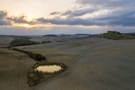Tuscany, Siena, October 20, 2019. Aerial view of a rural landscape during sunset in Tuscany. Rural farm, cypress trees, green fields, sunlight and clouds. Italy, Europe.