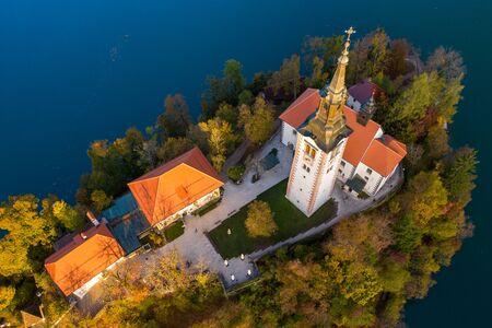 Luftaufnahme des bunten Waldes und des Bleder Sees mit einer kleinen Insel mit einer Kirche. Sonnenaufgang in Slowenien im Herbst.
