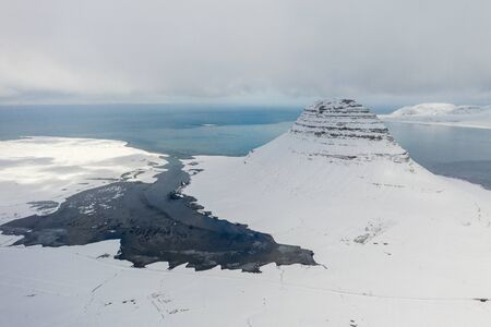 Aerial view of the snow-capped Mount Kirkjufell in early spring in Iceland.