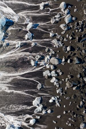 Aerial view of ice floes and icebergs on Diamond beach. The beginning of spring in Iceland.