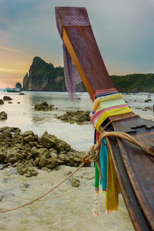 Thai long-tail boat sits on the beach at sunset.