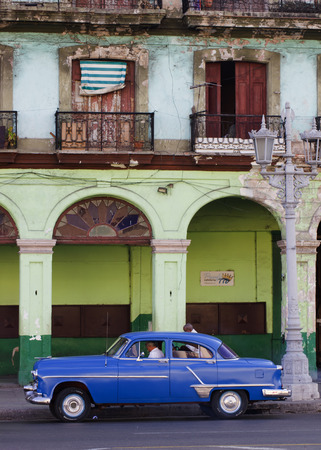 dilapidated: Blue Classic car in front of dilapidated building Editorial