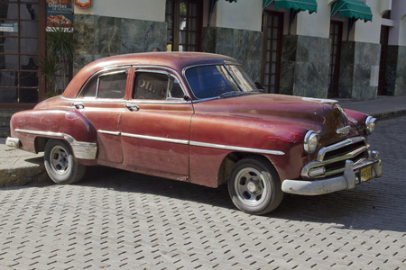 meant: Brown old classic car in a street in Havana  Past international embargoes have meant Cuba has maintained many pre-revolutions vehicles
