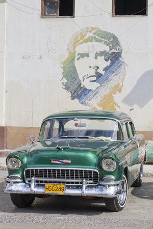 che guevara: Classic cuban car with mural of Che Guevara painted above