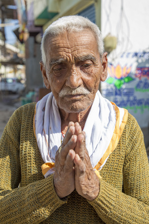 spoken: Old Indian man greeting with his palms together in a namaste gesture. Namast is spoken with a slight bow and hands pressed together, palms touching and fingers pointing upwards, thumbs close to the chest.  Editorial