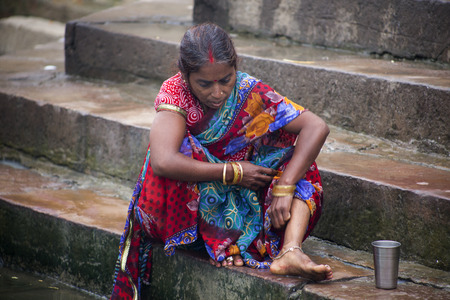 ghat: Woman bathing at the Ghat steps at the side of the Ganges River, Varanasi, India