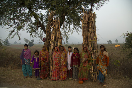 bindi: India, Madhya Pradesh - December, 31, 2014; Group of rural Indian women resting from carrying long loads of wood on their head