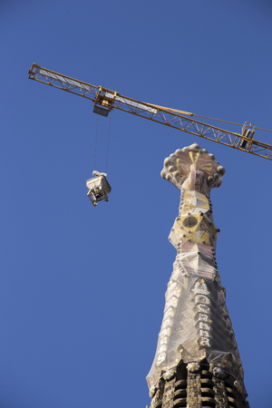 financed: Barcelona, Spain - September 22, 2015: Crane working on tower at Sagrada Familia, Work began on the unconventional church in 1882 and continues today, financed by public subscription.