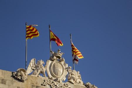 Patriotic Catalan Flags flying on top of Casa de la Ciutat, Barcelona, Spain