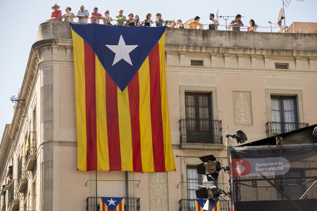 merce: Barcelona, Spain - September 20, 2015: A large Catalan flag , a symbol of Calalonian independence, hangs below onlookers watching the the La Merce performances in Sant Jaume Square.