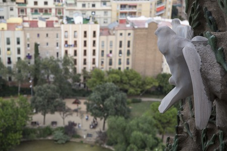 profound: Barcelona, Spain - September 21, 2015: A stone carved dove looks out over the Placa de Guadi from the Sagrada Familia.  Gaudis profound catholicism inspired his designs of Sagrada Familia.