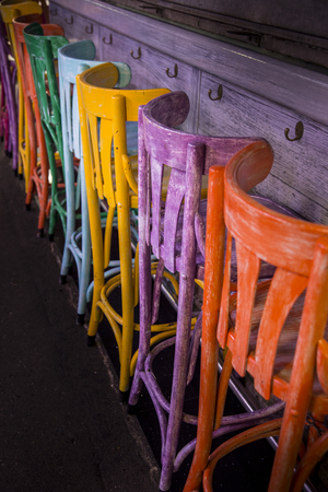 stools: Multi coloured stools at a conter in a market Stock Photo