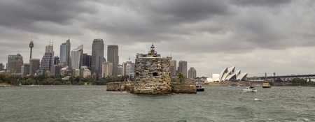 port jackson: Sydney, Australia - December 13, 2015: Fort Denison with the Sydney skyline behind. Fort Denison was a former penal colony and defensive facility and is now a tourist attraction in the middle of Sydney Harbour.