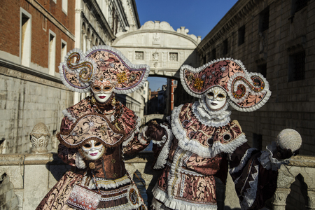 carnivale: Venice, Italy - February 6, 2016: Revellers in Venetian Carnivale Costumes in front of Bridge of Sighs. Authorities have increased surveillance throughout the city however, authorities rejected a proposal to ban revellers from wearing masks. Editorial
