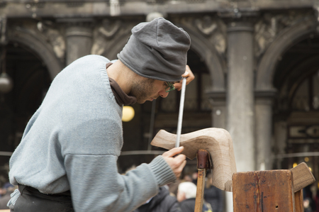carver: Venice, Italy - February 8, 2016 Gondola Artisan carver displays his skills at the Venice Carnival in San Marco Square to highlight the importance this untouchable cultural heritage handed down since the middle ages.