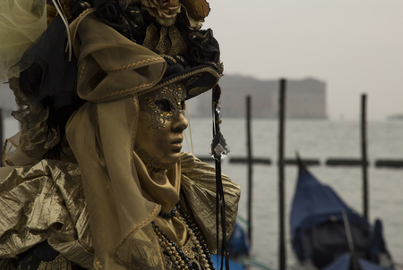 revellers: Venice, Italy - February 9, 2016: Reveller in Venetian Carnivale Costume. Authorities have increased surveillance throughout the city but rejected a proposal to ban revellers from wearing masks.