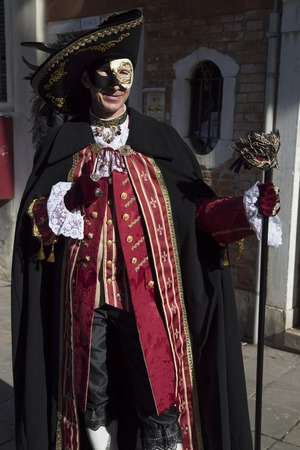 carnivale: Venice, Italy - February 6, 2016: Reveller in Venetian Carnivale Costume. Authorities have increased surveillance throughout the city but rejected a proposal to ban revellers from wearing masks.