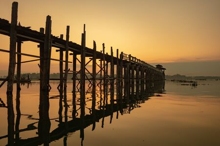 Sunrise view of the ancient teak wood U Bein Bridge that stretches across Taungthaman Lake at Amarapura, near the city of Mandalay in Myanmar (formerly called Burma)