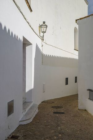 Dramatic shadows are cast on the bright whitewashed walls of a narrow street in the Andalusian village of Arcos de la Frontera, one of the pueblos blancos (white villages) in southern Spain 版權商用圖片