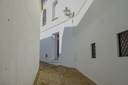 Dramatic shadows are cast on the bright whitewashed walls of a narrow street in the Andalusian village of Arcos de la Frontera, one of the pueblos blancos (white villages) in southern Spain