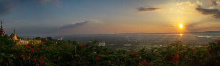View over the city of Mandalay at sunset from Mandalay Hill, with red flowers and golden pagodas, in Myanmar, formerly called Burma