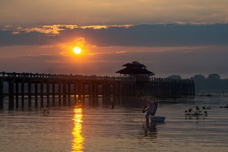 A fisherman stands in shallow water at sunrise in front of the ancient teak wood U Bein Bridge that crosses Taungthaman Lake at Amarapura, near the city of Mandalay in Myanmar (formerly called Burma)