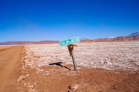 A signpost with a skull attached marks the dirt road across the Salar de Arizaro salt flats, near Tolar Grande in the high altitude desert of Salta's puna region in Argentina