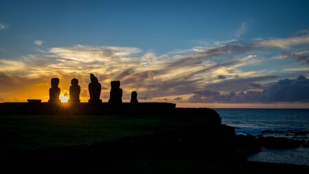 The sun sets behind the silhouetted, carved stone moai heads of Ahu Tahai, in the town of Hanga Roa on Rapa Nui, known as Easter Island, in the Pacific Ocean Stock Photo