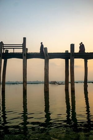 Buddhist monks are silhouetted by the sunrise as they walk across the ancient teak wood U Bein Bridge across Taungthaman Lake at Amarapura, near the city of Mandalay in Myanmar (formerly called Burma)