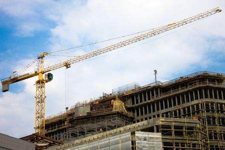 photo of the construction site with crane, building and workers photo