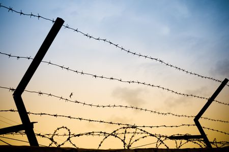 photo of old rusty barbed wire against sky photo