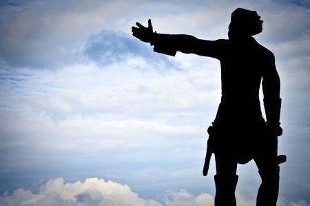 hist: statue of the man with hist hand directed to the blue sky with clouds