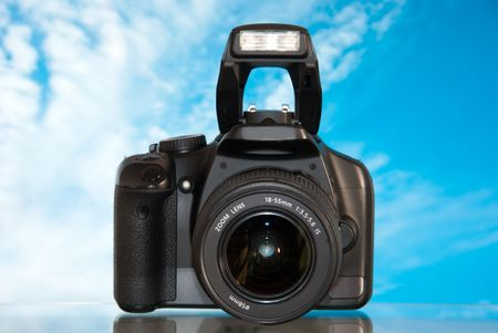 eos: Dslr camera isolated on sky background with reflection