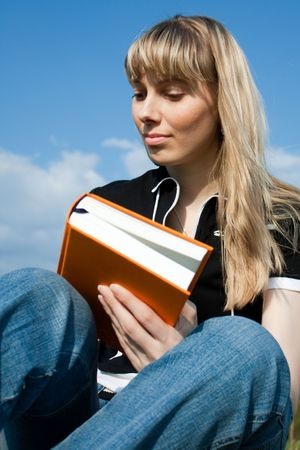 girl reading book and sitting outdoor with sky in background Stock Photo - 5157325