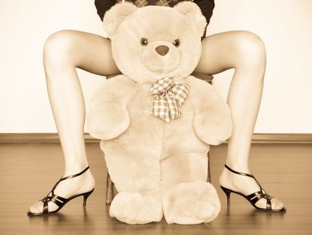 sepia photo of the toy bear between girl legs photo
