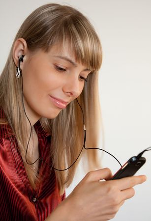 close up photo of the beautiful happy girl listening music on mobile phone photo