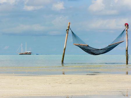 photo of the hammock on the beach and ship in the sea on background photo