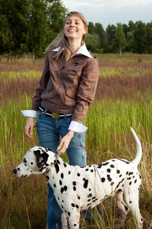 young smiling beautiful girl with blue sky in background standing in the  green grass with her dalmatian dog pet photo