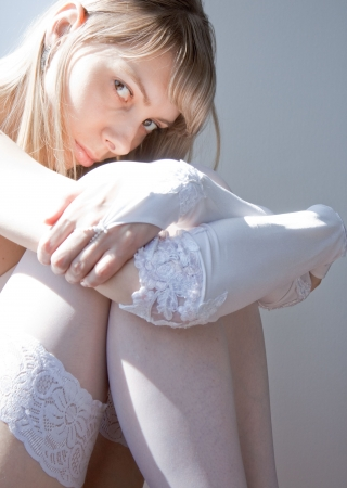 young blond sexy girl in white gloves and stockings sitting on the floor photo