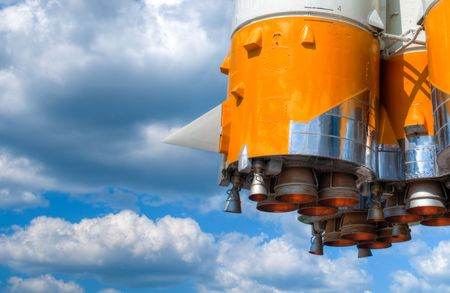 details of space rocket engine against blue sky with clouds photo